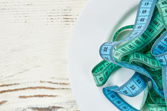 Measuring tape on a plate. Strategy for getting healthy Stock Photography