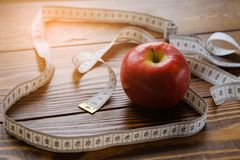 Measuring tape and red Apple on wooden background. The concept of diet, healthy lifestyle and proper nutrition. royalty free stock photos