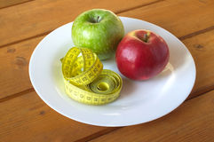 Measuring tape and ripe apples on plate Stock Photo