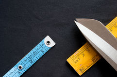 Measuring tape, scale and scissors on black cloth Royalty Free Stock Photography
