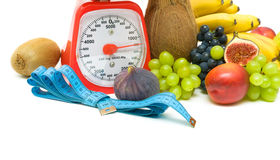 Measuring tape, scales and fruits on white background Stock Photography