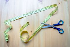Measuring tape and scissors lying on a wooden table royalty free stock photo