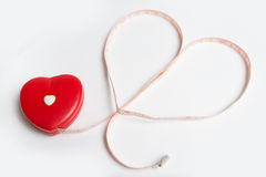 A measuring tape shaping a heart on white background royalty free stock photography