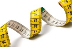 Measuring Tape Spiral. Winding tape measure against white Royalty Free Stock Photos
