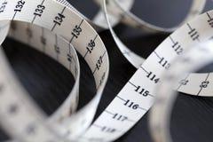 Measuring tape. Closeup. Measuring tape in a spiral. Closeup, macro. Fashion instrument Royalty Free Stock Photo