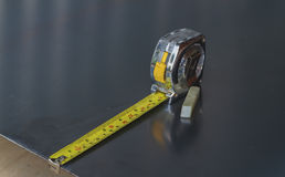 Measuring tape on a steel plate. Stock Image