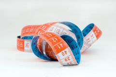 Measuring tape for tailor. Blue and orange spiral  measuring tape over white Royalty Free Stock Image