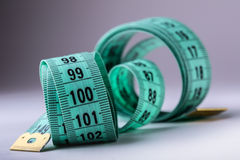Measuring tape of the tailor. Closeup view of white measuring tape Royalty Free Stock Image