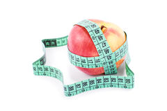 Measuring tape twisted around ripe apple Stock Photography