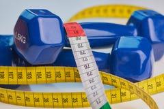 Measuring tape beside two blue dumbbells stock images