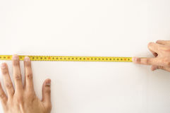 Measuring tape in wall white Stock Photography