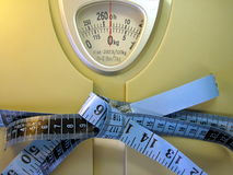 Measuring tape on weight scale Royalty Free Stock Images