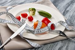 Measuring tape in a plate with fresh vegetables stock photo