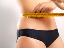 Measuring tape on a woman's waist Royalty Free Stock Photo
