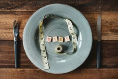 Measuring tape and word DIET in a plateon a wooden table. royalty free stock photo