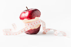 Measuring tape wrapped around apple as a symbol of diet. Royalty Free Stock Images