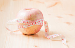 Measuring tape wrapped around apple as a symbol of diet, on wood Stock Images