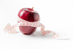 Measuring tape wrapped around apple in fat boy hand,as a symbol Stock Photos