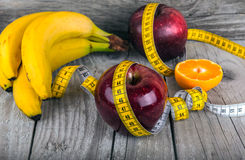 Measuring tape wrapped around a apple weight loss Stock Photo