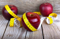 Measuring tape wrapped around a apple weight loss Stock Image