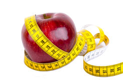 Measuring tape wrapped around a apple weight loss Royalty Free Stock Photography