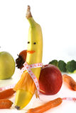 Measuring tape wrapped around a banana in the form of girl , with apple, broccoli and carrot. Concept diet. Measuring tape wrapped around a banana isolated on a Royalty Free Stock Images
