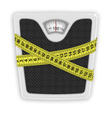 Measuring tape wrapped around bathroom scales. Concept of weight Royalty Free Stock Image