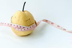 Measuring tape wrapped around a Chinese pear Stock Photo