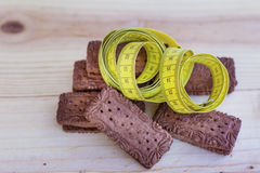 Measuring tape wrapped around chocolate biscuits Stock Photo