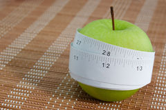 Measuring tape wrapped around a green apple Royalty Free Stock Photos