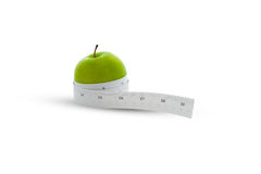 Measuring tape wrapped around a green apple Stock Photos