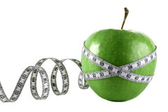 Measuring tape wrapped around a green apple as a symbol of diet. On a white background the green apple wound by meter stock images