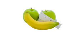 Measuring tape wrapped around a green apple and banana Royalty Free Stock Photos