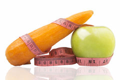 Measuring tape wrapped around a green apple and carrot Stock Photography