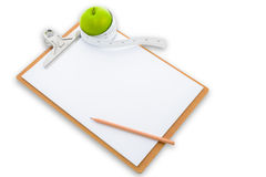 Measuring tape wrapped around a green apple and clipboard Royalty Free Stock Images