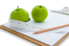 Measuring tape wrapped around a green apple and clipboard Stock Photo