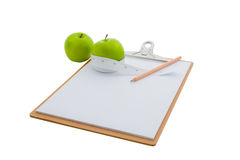 Measuring tape wrapped around a green apple and clipboard Stock Photography