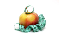 Measuring tape wrapped wave around an apple as a symbol of diet Royalty Free Stock Photography