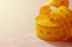 The measuring tape of yellow color with numerical indicators in the form of centimeters or inches lies on a gray knitted fabric. Background concept for sewing royalty free stock image
