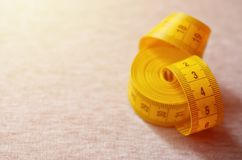 The measuring tape of yellow color with numerical indicators in the form of centimeters or inches lies on a gray knitted fabric. Background concept for sewing stock photos