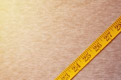 The measuring tape of yellow color with numerical indicators in the form of centimeters or inches lies on a gray knitted fabric. Background image about sewing stock image