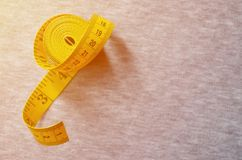The measuring tape of yellow color with numerical indicators in the form of centimeters or inches lies on a gray knitted fabric. Background concept for sewing stock images