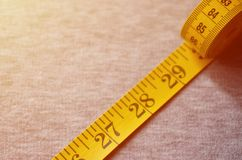The measuring tape of yellow color with numerical indicators in the form of centimeters or inches lies on a gray knitted fabric. Background concept for sewing stock image