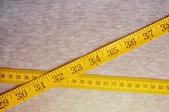 The measuring tape of yellow color with numerical indicators in the form of centimeters or inches lies on a gray knitted fabric. Background image about sewing stock photo