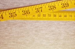 The measuring tape of yellow color with numerical indicators in the form of centimeters or inches lies on a gray knitted fabric. Background concept for sewing stock photo