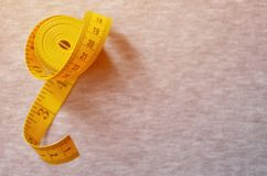 The measuring tape of yellow color with numerical indicators in the form of centimeters or inches lies on a gray knitted fabric. Background image about sewing royalty free stock photo