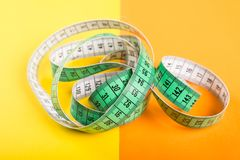 Measuring tape on yellow and orange background stock image