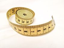Measuring Tape. Yellow measuring tape on a white cloth background Stock Photos