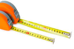 Measuring tapes. Two measuring tapes in orange cases, over white Royalty Free Stock Images