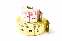 Measuring Tapes. White & Yellow Measuring Tapes coiled & stacked Royalty Free Stock Photo